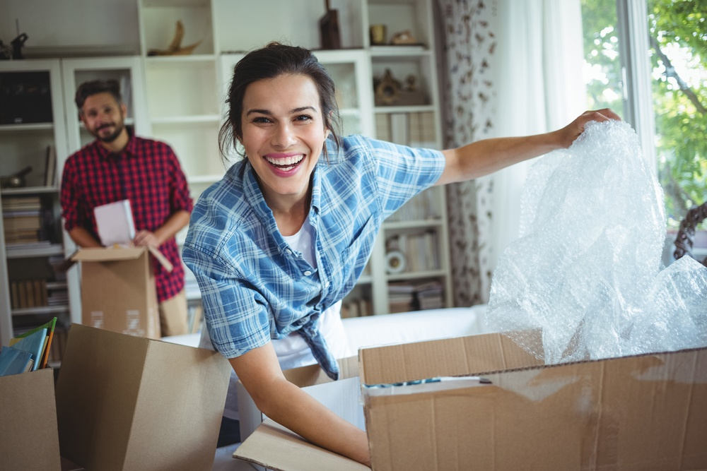 Happy couple unpacking cartons in their new house.jpeg