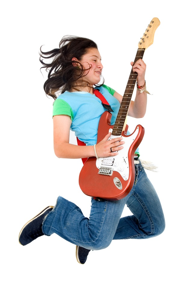 Teenage girl jumping whilst playing an electric guitar isolated over a white background.jpeg